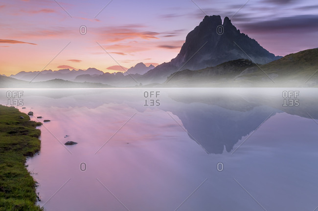 South West France, hazed sunset on the Pic D'Ossau with the lake Gentau in the foreground