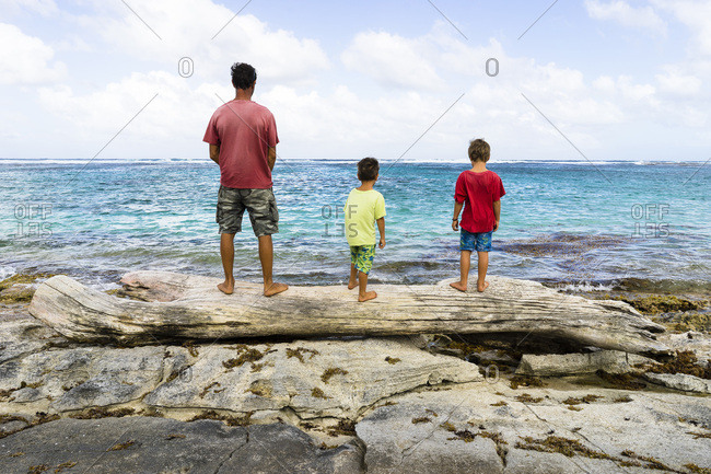 A father and his two sons looking at the sea, Capesterre, Marie Galante, Guadeloupe