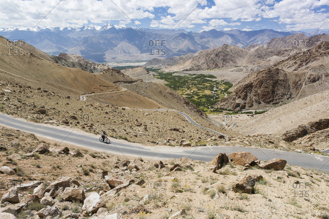 Woman cycling down the Khardung Pass route Connecting Leh to the Nubra Valley, the world's highest carossable road, 5,359 meters, Ladakh, India