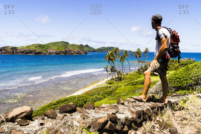 July 26, 2017: Man looking at the sea and an island, Petit Nevis, Saint-Vincent and the Grenadines, West Indies