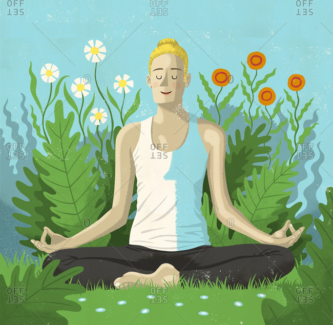 Man sitting in grass meditating by flowers