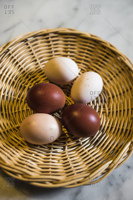 Assortment of farm eggs on wicker plate