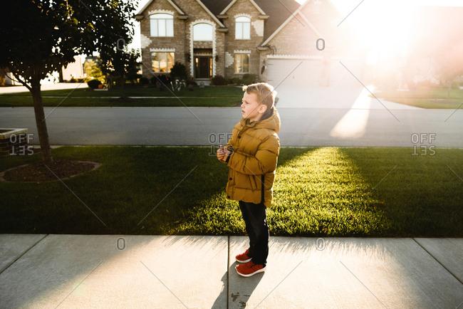 Boy standing on sidewalk wearing winter coat