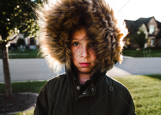 Boy wearing jacket with a furry hood