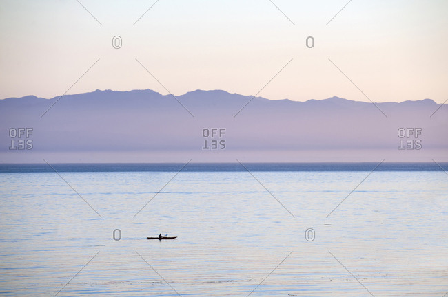 Kayaker off the coast of Victoria, Vancouver Island, British Columbia, with the Olympic Mountains of Washington in the background