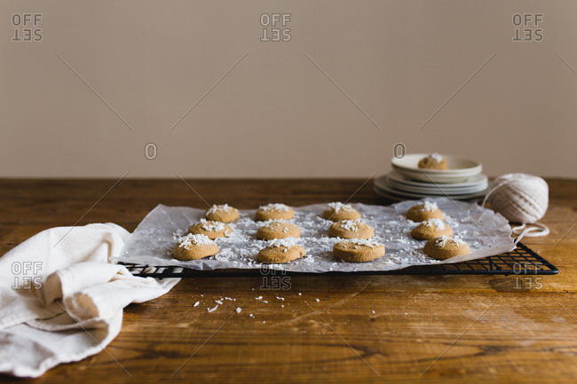 Cookies topped with coconut on parchment paper and cooling rack