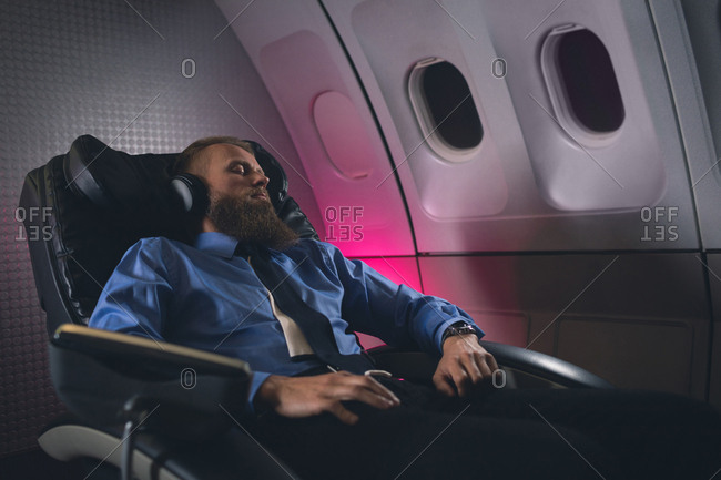 Businessman sleeping while listening to music in airplane