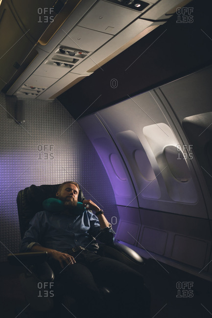 Businessman sleeping with neck pillow in airplane