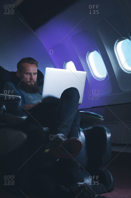 Businessman using laptop while travelling in airplane