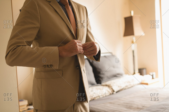 Man wearing his blazer in bedroom at home