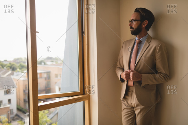 Man in full suit looking through window at home