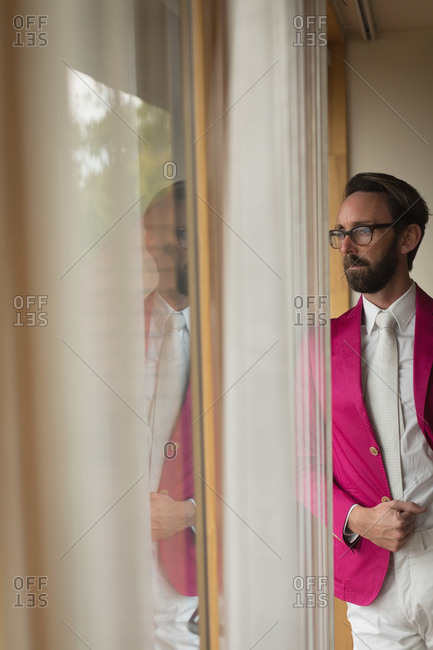 Man in suited looking through window at home