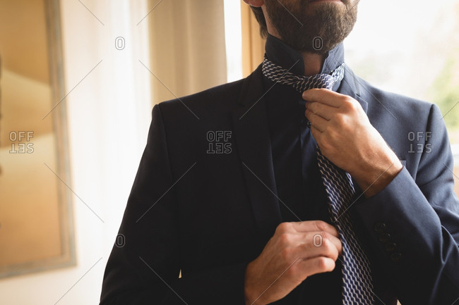 Mid section of man wearing his tie at home