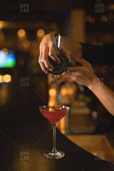 Waiter preparing cocktail drink at counter in chocolate bar
