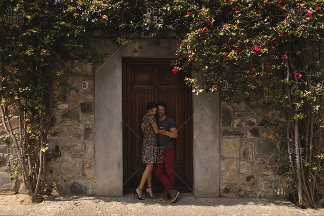 Couple embracing each other against door on a sunny day