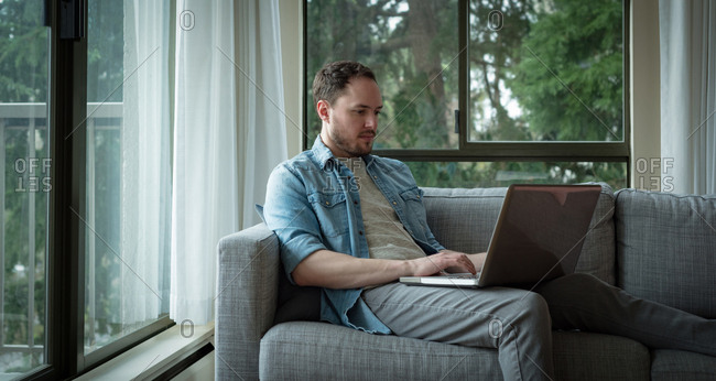 Man using laptop in living room at home