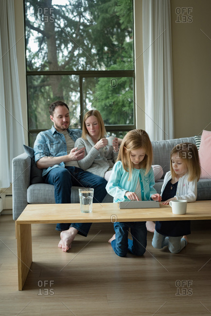Parents using mobile phone while children using digital tablet at home