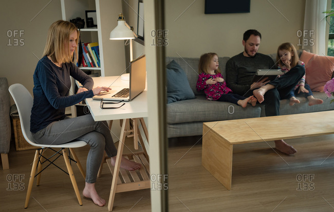Mother using laptop while father and daughters using digital tablet at home