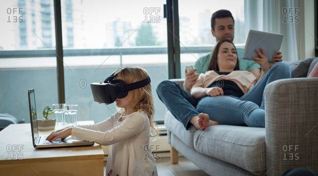 Parents using digital tablet while daughter using virtual reality headset at home