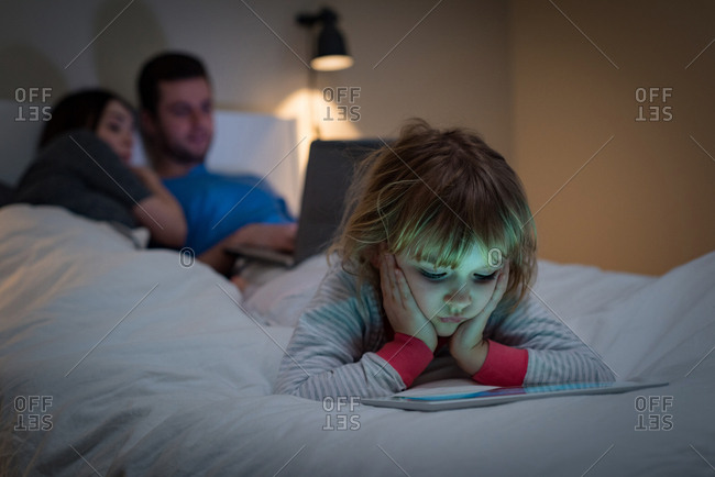 Girl using digital tablet while parents using laptop in bedroom at home
