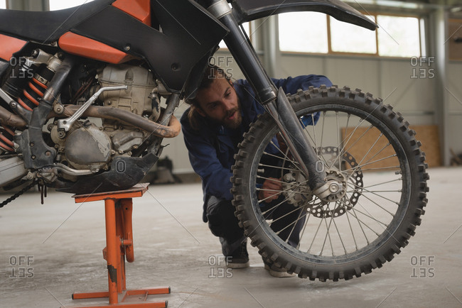 Mechanic repairing motorcycle in garage