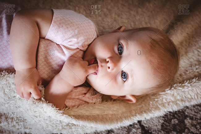Portrait of cute baby lying on blanket