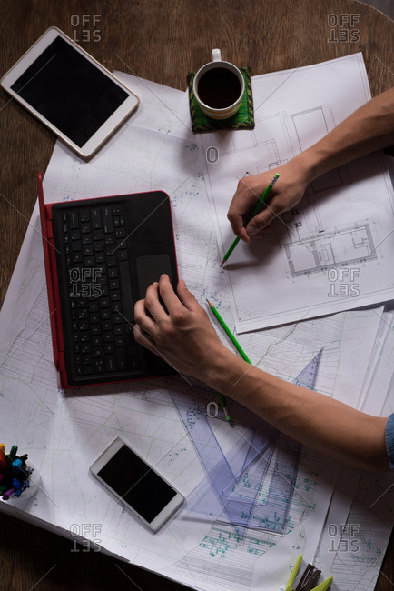 Male graphic designer working on laptop and blueprint in office