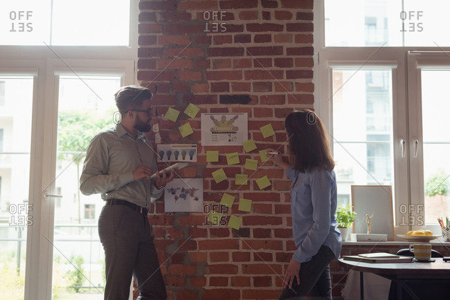 Executives discussing over sticky notes in office