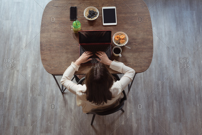 Female executives using laptop while having breakfast in office