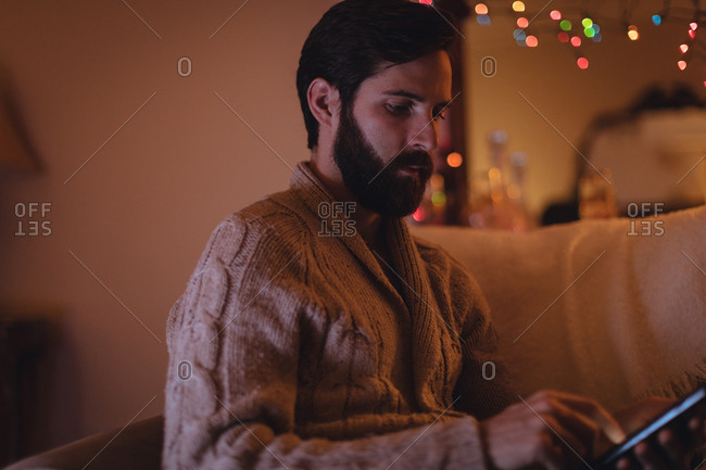 Man using digital tablet in living room at home