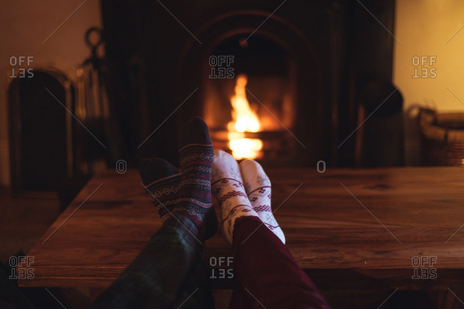 Couple feet in knitted woolen socks warming near burning fireplace at home