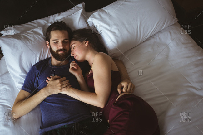 Couple sleeping together on bed in bedroom at home