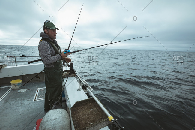 Fisherman fishing with fishing rod from the boat