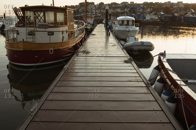 Moored boat and empty jetty at harbor during dusk