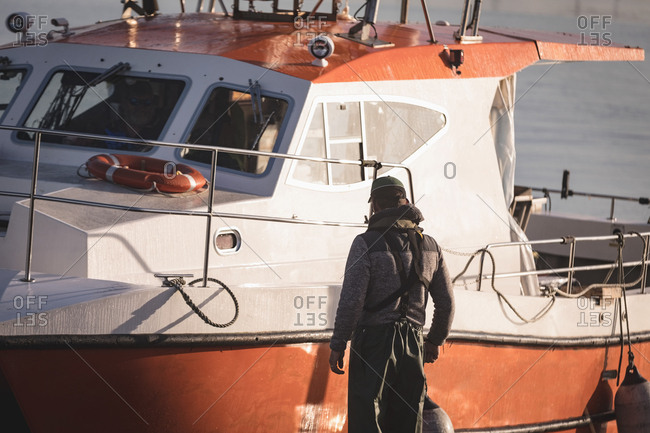 Fisherman standing with buoy near boat during morning