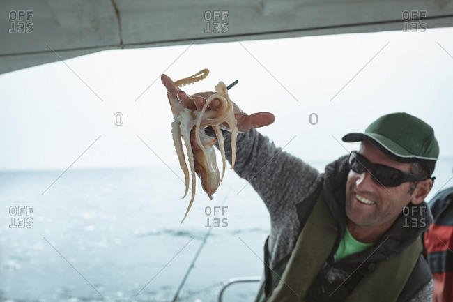 Fisherman holding octopus in boat