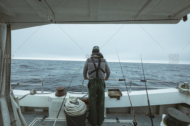 Rear view of fisherman standing on boat