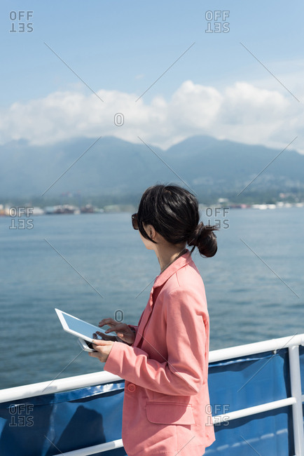 Close-up of woman with digital tablet looking at the mountains from ferry