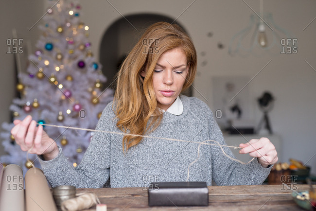 Blonde woman wrapping a Christmas gift with twine