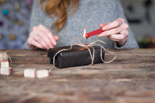 Woman putting wax seal on a gift