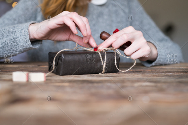 Hands of a woman putting wax seal on a gift