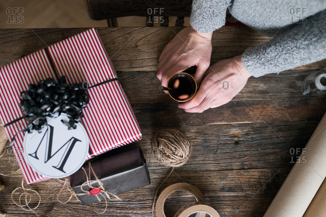 Woman drinking glogg while wrapping gifts