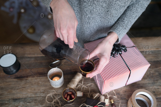 Woman pouring glogg while wrapping gifts
