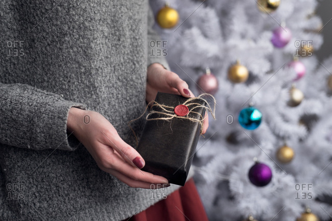 Hands of a woman holding a gift by a white Christmas tree
