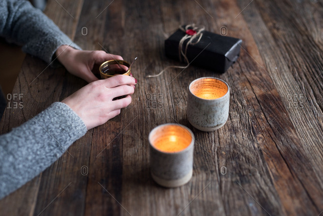 Woman drinking glogg beside candles and a gift