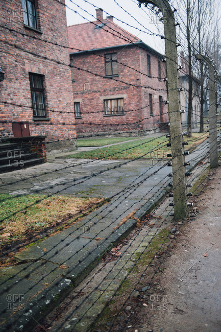 Barbed wire fences and brick buildings at Auschwitz-Birkenau