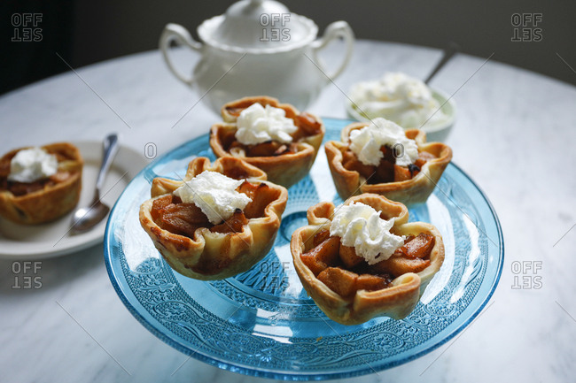 Mini apple tarts topped with whipped cream