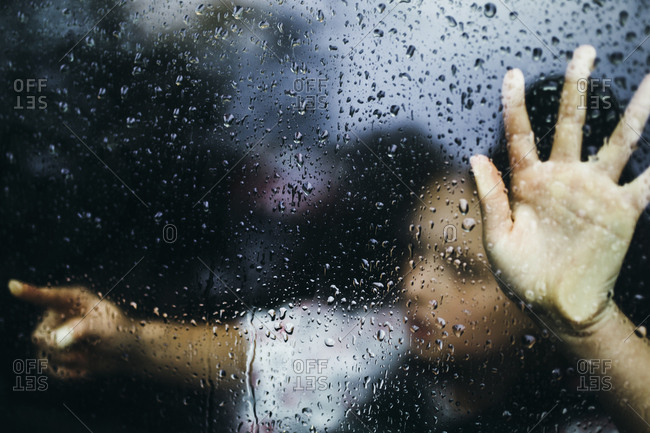 Little girl pointing behind rain covered window