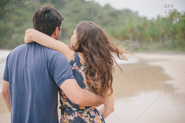Couple with their arms around each other walking together on the beach