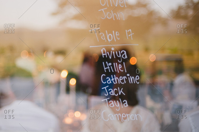 Table assignments for guests written on reflective surface at wedding reception